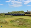 A train races by the first green of the Old Course at Prestwick Golf Club.