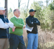From left, Beacon Land Development partners Casey Paulson and Michael Abbott meet with Tiger Woods during a site visit to Bluejack National.