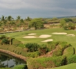 The 11th hole at The Club at Hokuli'a drops to a green guarded by a pond and bunkers.