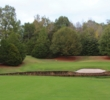 The sixth hole at Old Waverly Golf Club bends right to a green behind a pond.