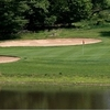 A view over the water of green protected by bunkers at Needwood Golf Course
