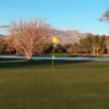 A view of green with water coming into play and mountains in background at Trini Alvarez El Rio Municipal Golf Course