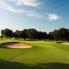 A sunny view of green flanked by sand traps at KickingBird Golf Club
