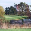 A fall view of a green with a bridge in foreground at Boone Links Golf Course