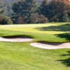 A sunny view a of a green protected by sand traps at Moselem Springs Golf Club
