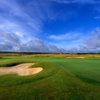 A view of green guarded by bunker at Machynys Peninsula Golf & Country Club