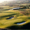 A sunny view of a green guarded by bunkers at Woodspring Golf & Country Club