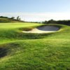 A sunny view of a hole protected by a bunker at White Cliffs Country Club
