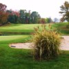 A fall view of a green guarded by a pond and sand trap at Traditions Golf Club