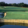 A view of a green surrounded by water at Lantana Golf Club
