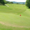 A view of a green with a narrow path in the left background at Kirkcudbright Golf Club