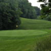 A view of a green with a narrow path in background at Gunpowder Golf Club