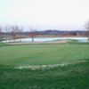 A view of a green with water in background at The Pines from Lindsey Wilson