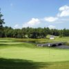 A view of a green with water in background at Indian Pond Country Club