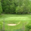 A view of a green protected by a bunker at Fox Run Country Club