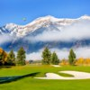 A view of a hole with mountain in background at Jackson Hole Golf & Tennis Club