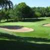 A sunny day view of a hole surrounded by sand traps at Reid Golf Course