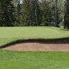 A view of a green protected by a bunker at Willow Park Golf and Country Club