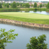 A view of a green surrounded by water at Dominion Valley Country Club
