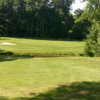 A view of a green protected by a pond and a bunker at Stone Dock Golf Club