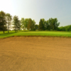 A view of a green protected by a large bunker at Willow Brook Golf Club