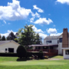 A view of the practice area and the clubhouse at Maplehurst Country Club