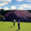 View of a green and clubhouse at Hadden Hill Golf Club