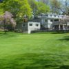 A view of a green and the clubhouse at Bellevue Golf Club