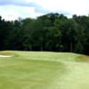 A view of a green flanked by bunkers at Oak Hill Country Club