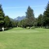 A view of a green with mountains in the distance at Ironwood Green Golf Course