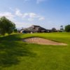 View of a green with the clubhouse in the background at Dudsbury Golf Club
