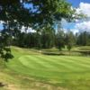 A sunny day view of a green with water on the right side at Billeruds Golf Club.