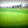 A view of the practice putting green and a fairway in background at Stillwater Golf Course.