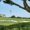A view of the clubhouse and a green surrounded by bunkers at Country Club of Florida.