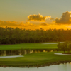 A sunset view of green #4 surrounded by water at Hideout Golf Club.
