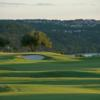 A view of a green with water in background at University of Texas Golf Club.