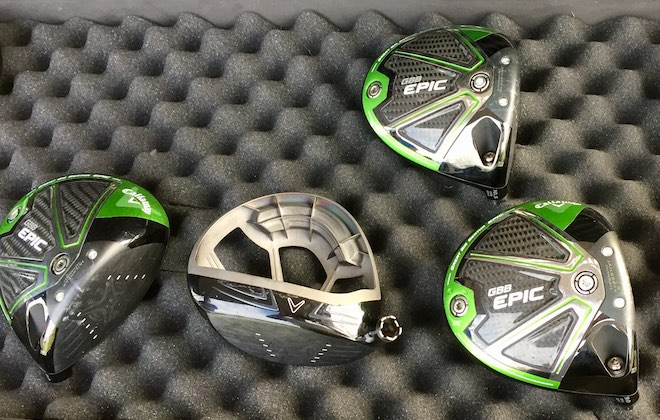 Callaway Epic driver heads waiting to be paired with any of a range of different shaft options. The one in the middle has had its crown detached to expose the club's inner workings.